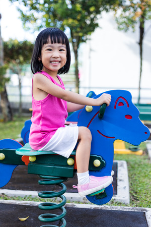 Asian Chinese little girl on seesaw at outdoor playground. Stock Photo