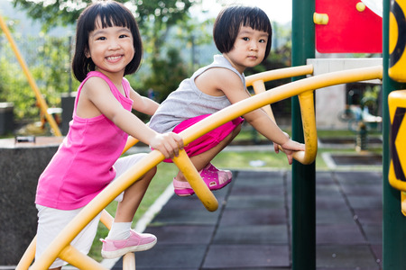 Asian Chinese little girl climbing at outdoor playground.