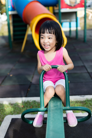 see saw: Asian Chinese little girl on seesaw at outdoor playground. Stock Photo