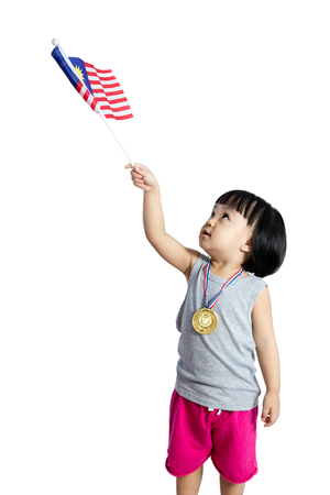 Asian Chinese little girl holding Malaysia Flag with gold medal in isolated plain white background. Stock Photo