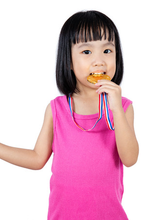 Asian Chinese little girl biting gold medal in white isolated background.