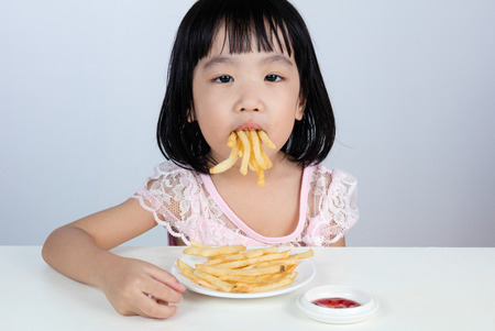 Asian Chinese little girl Refusing Eating French fries with clean isolated background.