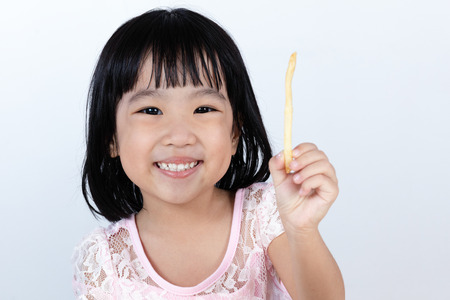 child smile: Happy Asian Chinese little girl Eating French Fries at indoor isolated clean background.