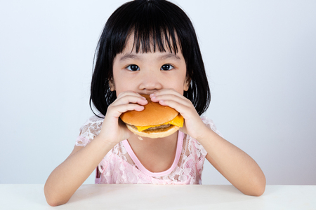 bollos: Asian Chinese little girl Eating Burger indoor with isolated clean background.