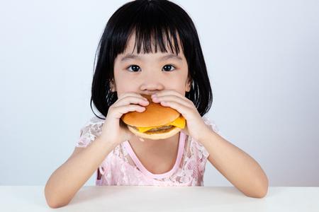 bollos: Niña asiática china que come la hamburguesa cubierta con fondo blanco limpio.