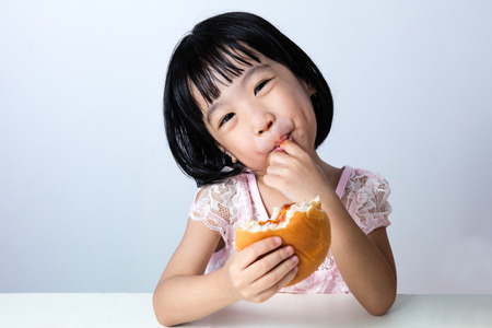 humourous: Asian Chinese little girl Eating Burger indoor with isolated clean background.