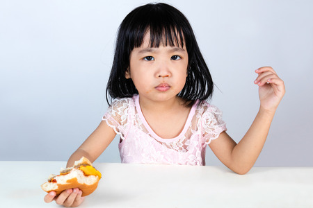 reluctance: Asian Chinese little girl Refusing Eating Burger with clean isolated background.