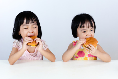 Asian Chinese little girl Eating Burger indoor with isolated clean background.
