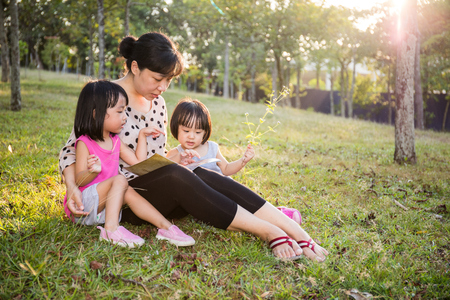 Asian Chinese Mother and Daughters Reading at outdoor Park