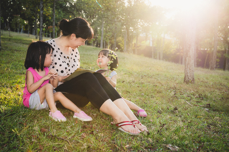 kid book: Asian Chinese Mother and Daughters Reading at outdoor Park