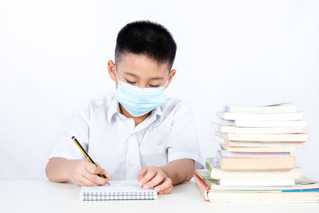 Asian Chinese Student Boy Writing with Protection Mask in plain isolated white background.