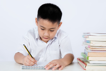 Asian Chinese Little Boy Wearing Student Uniform Writting Homework in plain isolated white background.