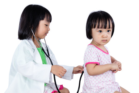 physician: Asian Chinese Little Sister Role Playing As Doctor and Patient in isolated white background.