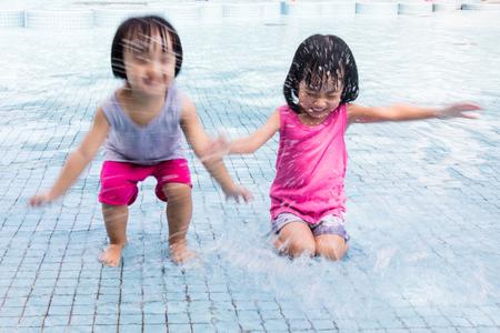 niñas chinas: Asian Chinese Little Girls Splashing at the pool outdoor. Foto de archivo