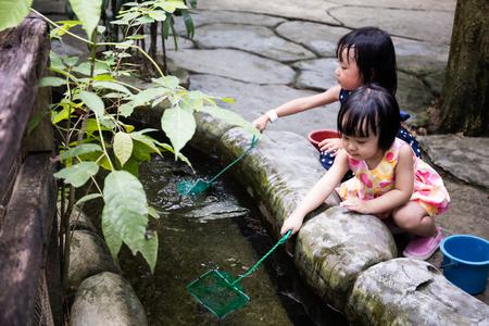niñas chinas: Pesca asiática china niñas con la cucharada neto al hecho-hombre al aire libre de la charca