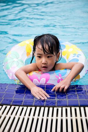 niñas chinas: Asiáticos chinos niñas nadar en la piscina al aire libre con el anillo inlfatable. Foto de archivo