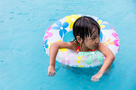 niñas chinas: Asian Chinese Little Girls Swimming In The Outdoor Pool with inlfatable ring.