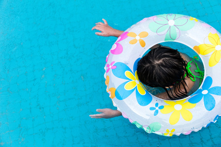 aquapark: Asian Chinese Little Girls Swimming In The Outdoor Pool with inlfatable ring.