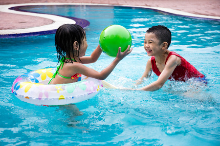 Asian Chinese Little Kids Playing in the outdoor Swimming Pool Stock Photo