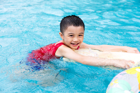 asian boy: Happy Asian Chinese Little Boy Swimming With Floating Board at Outdoor Swimming Pool.