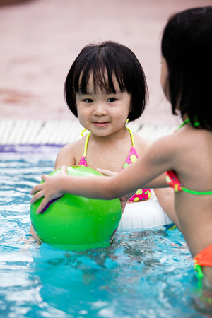 niños sanos: Asian Chinese Little Girls Playing in the Outdoor Swimming Pool Foto de archivo