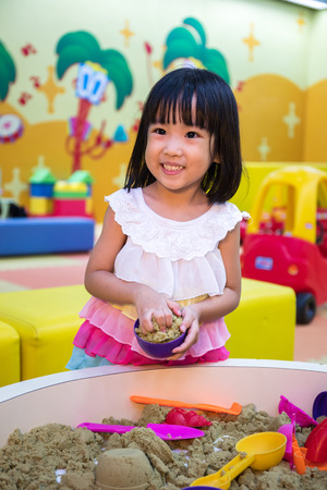 Happy Asian Chinese Little Girl Playing Kinetic Sand At Indoor Playground.