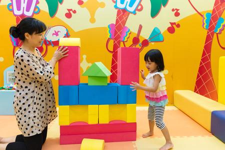 アジア中国ママと娘の屋内遊び場で巨大な積み木。