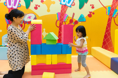Asian Chinese Mom and Daugther Playing Giant Blocks At Indoor Playground.