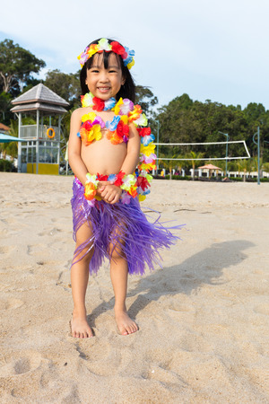 Asian Chinese little girl in hawaiian costume at beach outdoor.