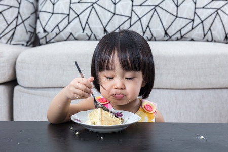 Moody Asian Chinese little girl eating birthday cheese cake at home indoor.