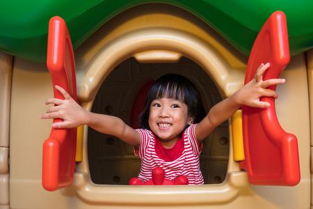 屋内の遊び場でおもちゃの家で遊んでアジアの中国少女。