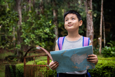 Asian Chinese little boy holding map in the forest searching for direction. Stock Photo