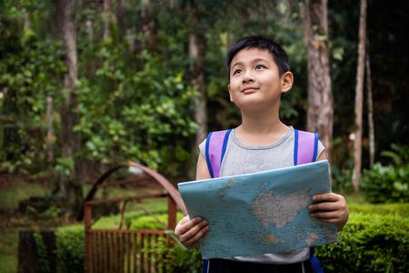 Niño pequeño asiático chino celebración mapa en el bosque en busca de dirección.