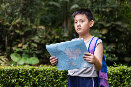 mapa china: Asian Chinese little boy holding map in the forest searching for direction. Foto de archivo