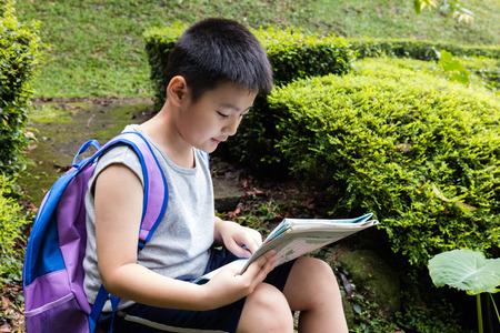 mapa de china: Asia chino niño pequeño que sostiene correspondencia que se sienta en la roca en el bosque Foto de archivo