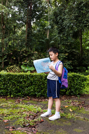 mapa de china: Asian Chinese little boy holding map in the forest searching for direction. Foto de archivo