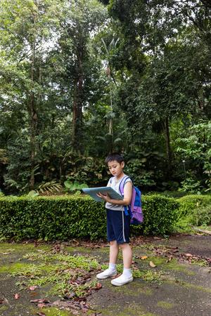 mapa de china: Niño pequeño asiático chino celebración mapa en el bosque en busca de dirección.