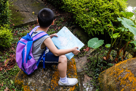 Asian Chinese little boy holding map sitting on the rock in the forest Stock Photo