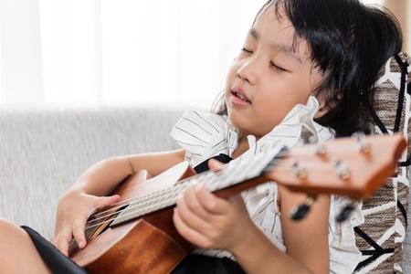 instruments de musique: Asiatique petite fille chinoise assis au canapé jouer ukele.