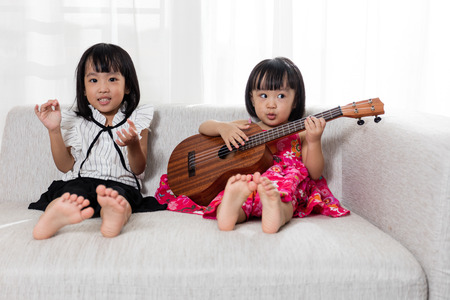 Asian Chinese little sister sitting on the sofa playing ukele