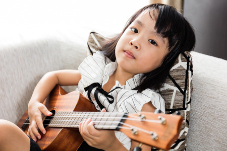 Asian Chinese little girl sitting at the sofa playing ukele.