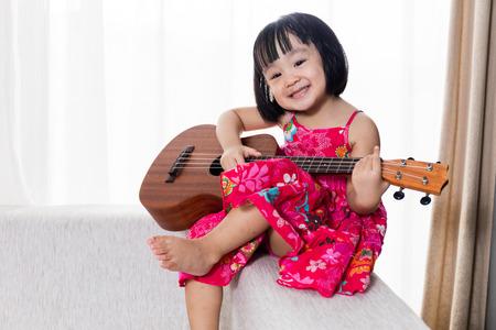 Happy Asian Chinese little girl sitting on the sofa playing ukele