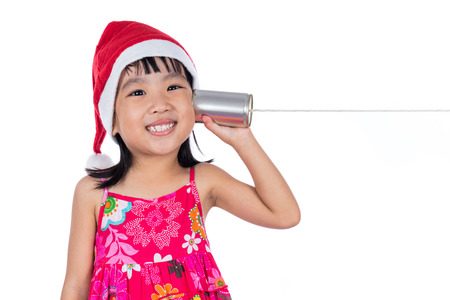 Asian Chinese little girl wearing santa hat holding tin can phone in isolated white background.