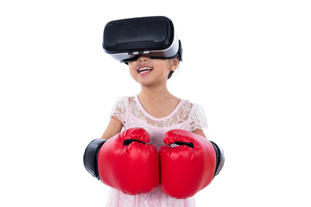 asian children: Asian Chinese little girl experiencing virtual reality with boxing gloves in isolated white background.