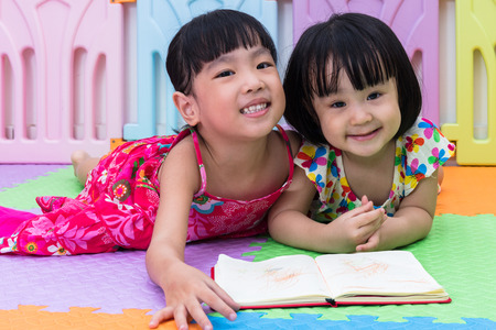 Asian Chinese little sisters laying on the floor reading at home