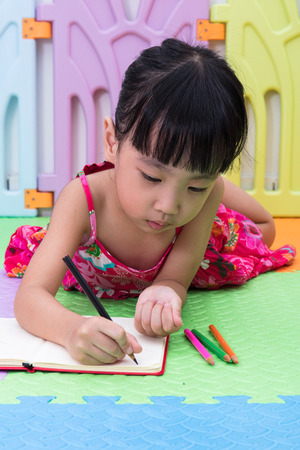 Asian Chinese little girl laying on the floor coloring at home