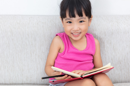 Happy Asian Chinese little girl sitting on sofa writting book in the living room.