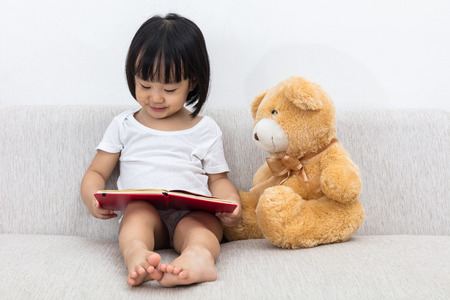 アジア中国小さな女の子本を読んでテディベアとリビング ルームのソファの上。