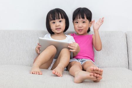 niñas pequeñas: Asiáticos pequeñas hermanas chinos que usa la tableta en el sofá de la sala de estar. Foto de archivo
