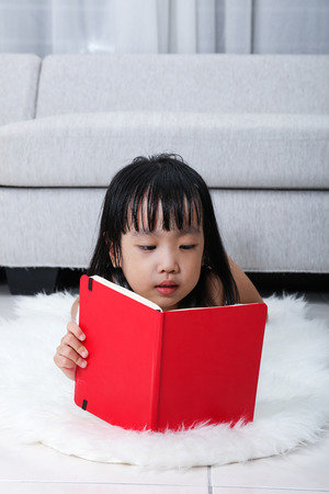 living wisdom: Asian Chinese little girl reading book on the floor in the living room at home.